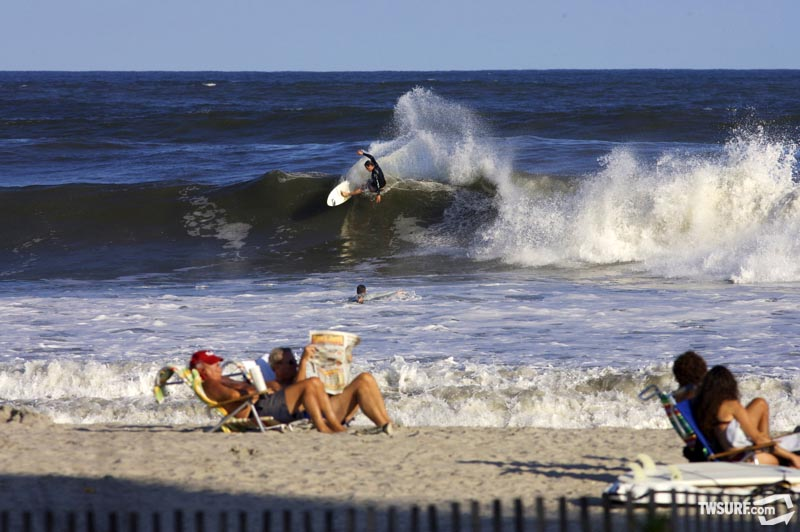 New Jersey's Zach Humphries throws down a big hack while a few late summer beachgoers get in one last bronzing session. Photo: Stafford/SPL